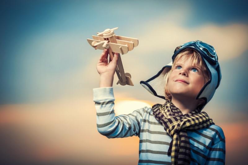 bambino che gioca con un aeroplano di legno