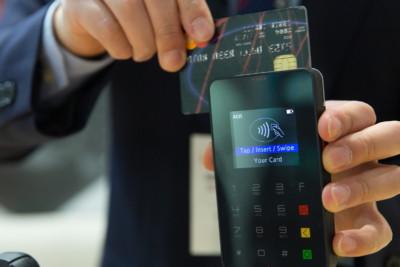 Un uomo passa la carta di credito sul cellulare