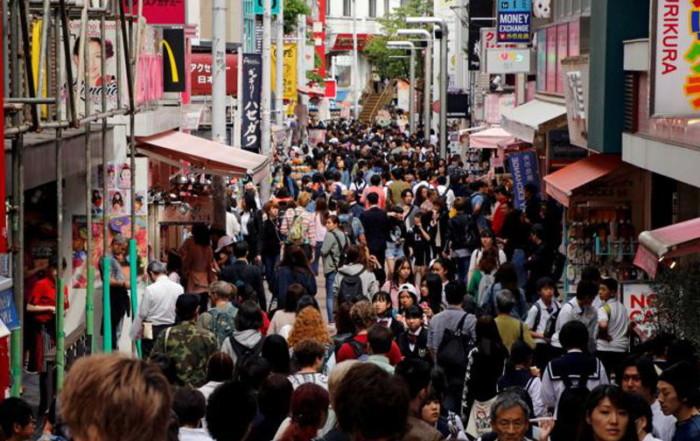 Persone in una via piena di negozi